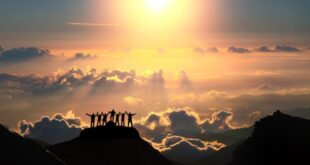 On the top of the world together. A group of people stands on a hill over the beautiful cloudscape.